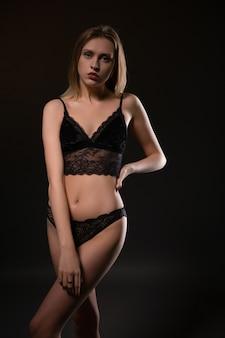 Sexy blonde frau mit einer wunderschönen figur in schwarzer spitzenunterwäsche