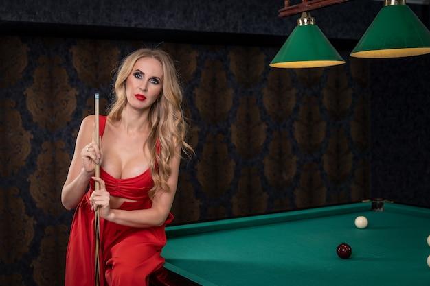 Sexy blonde frau sitzt auf der kante des billardtisches und hält ein stichwort