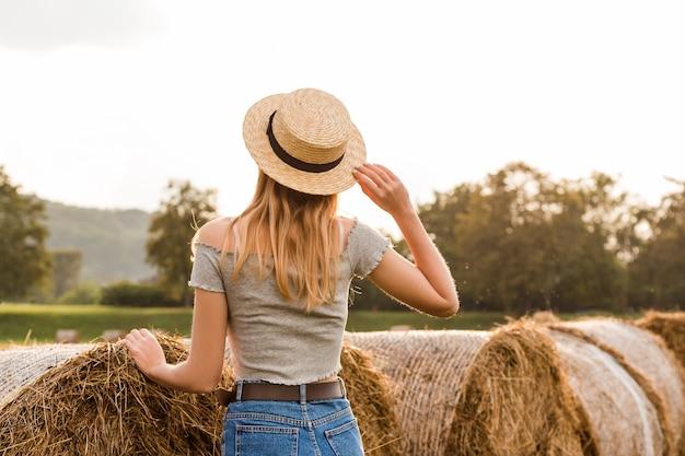 Sexy blondes mädchen auf heuhaufenrolle auf geerntetem weizenfeld im sommer. selektiver fokus. frau steht zurück