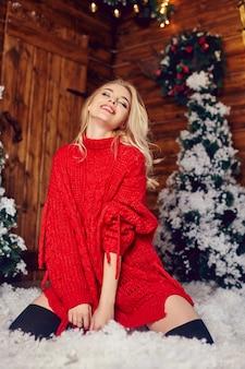 Sexy blondes mädchen in der roten strickjacke, die spaß in einem raum mit weihnachtsdekoration hat