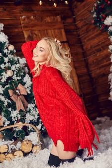 Sexy blondes mädchen in der roten strickjacke, spaß habend