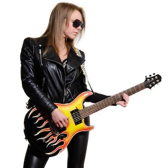 Sexy blondes mädchen in der schwarzen lederjacke der sonnenbrille, die schwarze e-gitarre spielt
