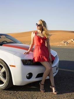 Sexy blondes mädchen sitzt auf cabrio-motorhaube in der wüste