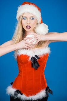 Sexy blondes modell in der kleidung des weihnachtsmannes schönes sexy mädchen hält weißen weihnachtsball in den händen