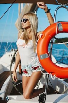 Sexy blondes modellmädchen mit schlankem körper in den jeansshorts und im weißen t-shirt, die auf einem yachtschiff am meer aufwerfen