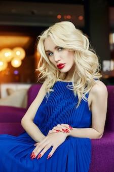 Sexy blondine im blauen kleid, das in einem stuhl sitzt