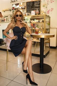 Sexy blondine im kurzen kleid und in gläsern, die im café sitzen