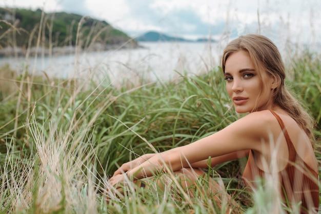 Sexy blondine in einem roten bodysuit, der das sitzen im gras unter einem feld mit den ährchen aufwirft