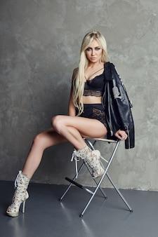 Sexy blondine in schwarzer unterwäsche und lederjacke