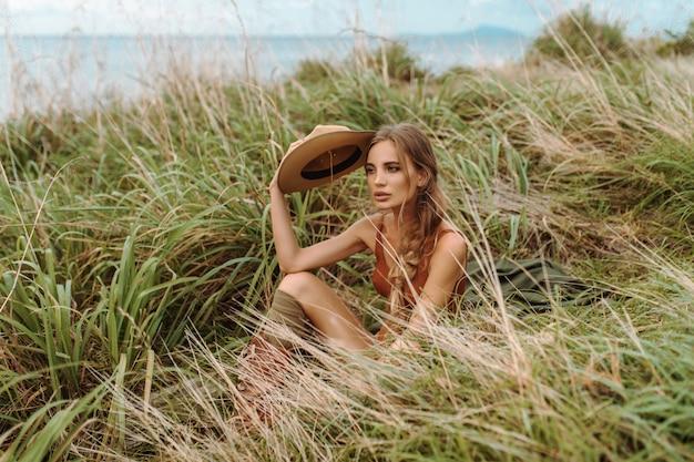 Sexy blondine mit einem umsponnenen zopf und einem hut am kopf in einem roten bodysuit von hellgrünen gamaschen und von stiefeln, die das sitzen im gras unter einem feld mit den ährchen aufwerfen