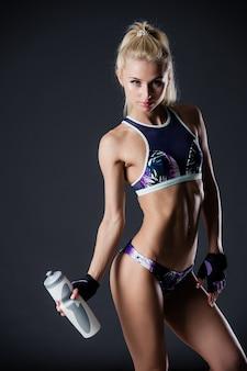 Sexy blondine mit langen haaren und sportlichem aussehen posiert