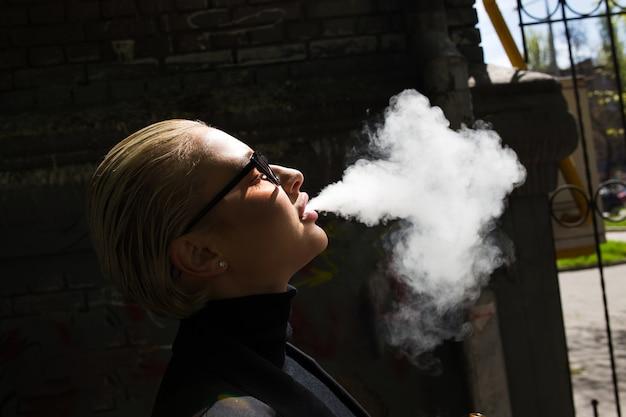 Sexy blondine raucht und setzt rauch frei