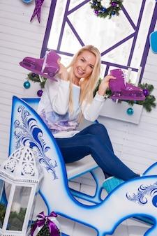 Sexy blondine sitzt auf einem weihnachtsschlitten auf einer weißen terrasse