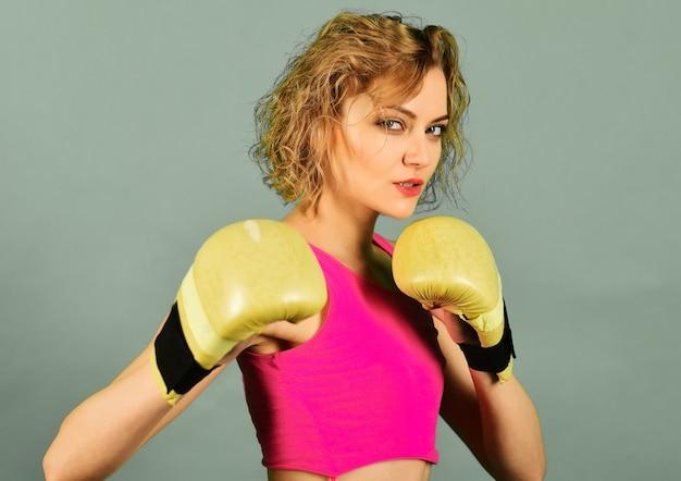 Sexy boxermädchen in sportkleidung und boxhandschuhen. sport und fitness, kraft und bewegung. gesundes lebensstilkonzept.