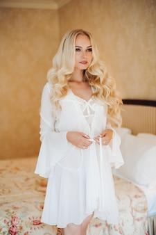Sexy braut, die in der weißen spitzewäsche am luxusschlafzimmerinnenraum trägt