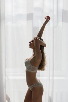 Sexy brünette des schönen mädchens in der weißen unterwäsche, die in einem raum im innenraum aufwirft