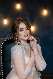 Sexy brünette des schönen mädchens in der weißen unterwäsche, die in einem raum im innenstudio aufwirft