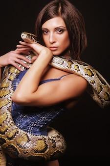 Sexy brünette, die python über schwarzem hintergrund hält