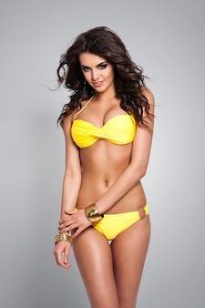 Sexy brünette frau, die im gelben bikini aufwirft