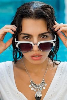 Sexy brünette frau, die nahe pool in der stilvollen sommerkleidung sitzt. tropischer urlaub.