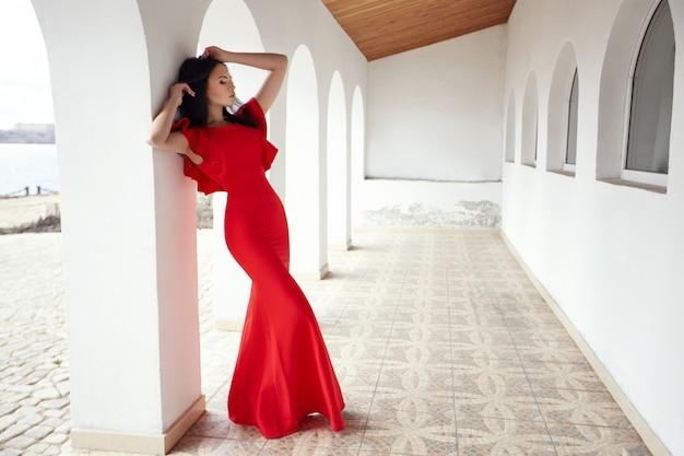 Sexy brünette frau im roten kleid steht in der nähe der mauern der alten villen am meer. porträt einer mädchennahaufnahme, romantische sexuelle weise. haare im wind gewickelt. sommer, urlaub, reisen