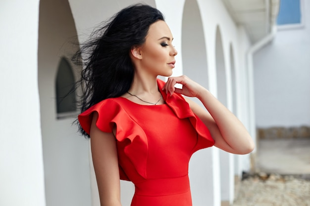 Sexy brünette frau im roten kleid steht in der nähe der mauern der alten villen am meer