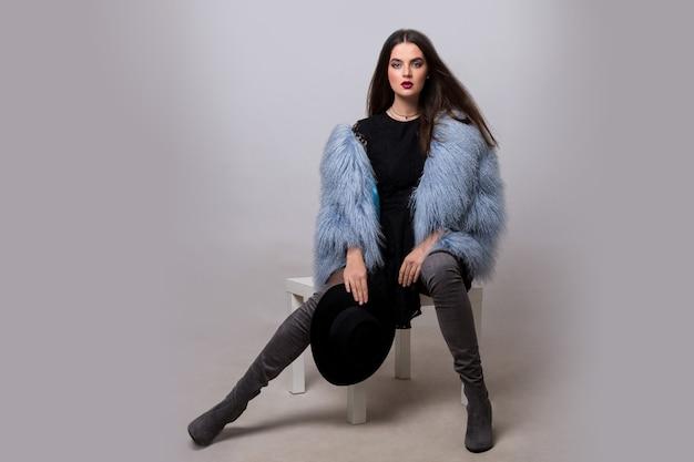 Sexy brünette frau in trendiger blauer pelzjacke und samthohen hohen stiefeln, die auf grauer wand aufwerfen.