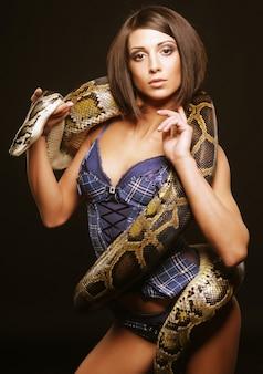 Sexy brünette hält python über schwarz
