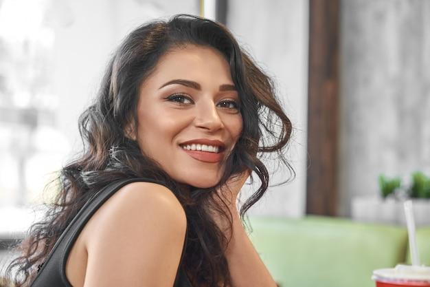 Sexy brünette im schwarzen t-shirt mit schönem lächeln im café.