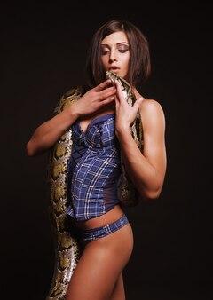 Sexy brünette mit python auf schwarzem hintergrund