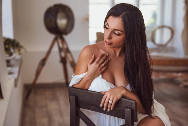 Sexy brunette, der am fenster in einem weißen kleid sitzt