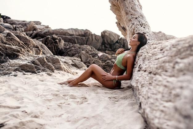 Sexy brunette des schönen mädchens im badeanzug, der auf strand nahe altem baum aufwirft