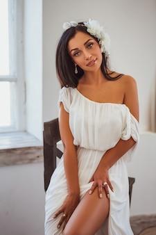Sexy brunette im weißen kleid, das am fenster sitzt