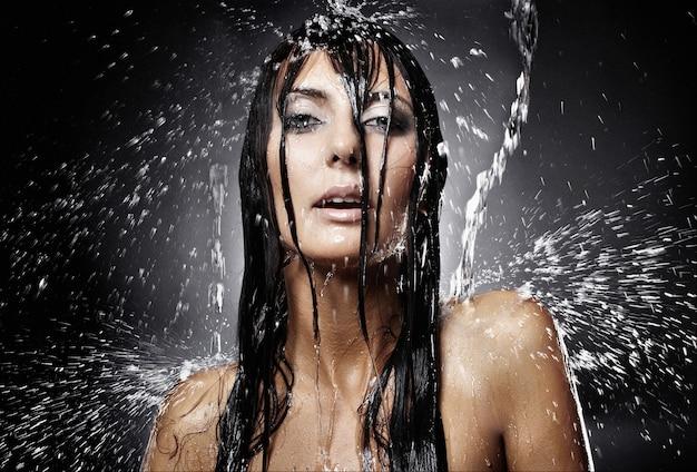 Sexy brunettefrau, die in der wäsche im regen aufwirft
