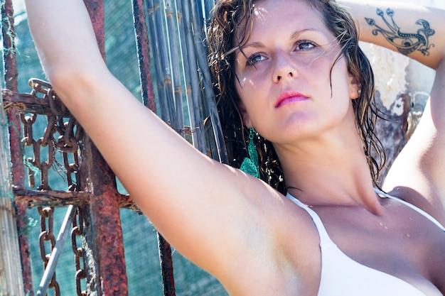 Sexy brunettefrau im weißen bikini, der draußen gegen stahltor aufwirft