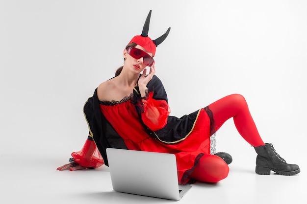 Sexy brunettefrau in den roten strumpfhosen, in den schwarzen stiefeln und in den teufelhörnern, die mit laptop über weißer studiowand aufwerfen