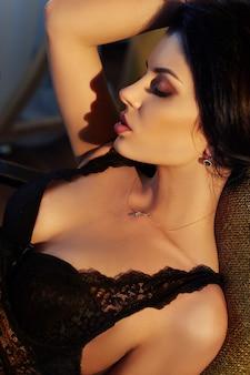 Sexy brunettefrau in der wäsche zu hause, die auf einem stuhl sitzt. perfekte figur, schöner körper an der frau. glatte, saubere haut und langes, kräftiges haar. die frau im licht der gelben lampe