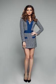 Sexy brunettemädchen mit dem langen gewellten haar im eleganten bürokleid und -fersen.
