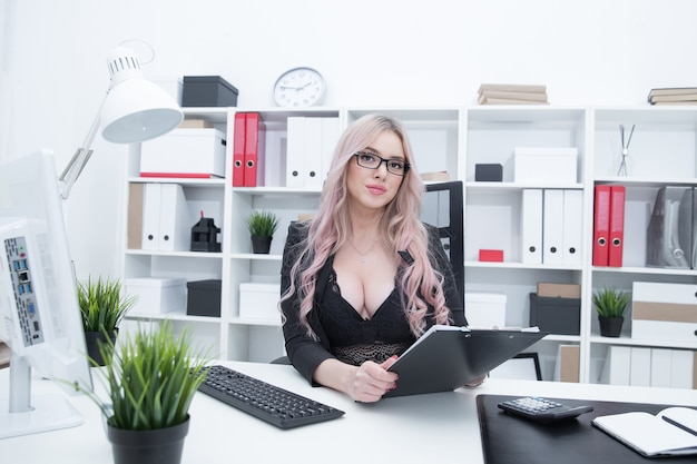 Sexy büroleiterin, die am schreibtisch arbeitet