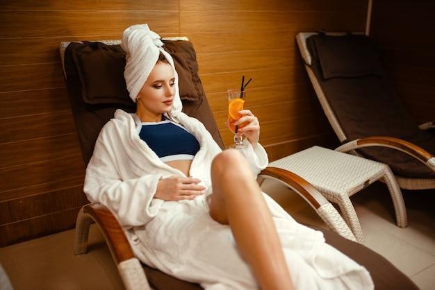 Sexy dame, die mit cocktail im spa-stuhl entspannt
