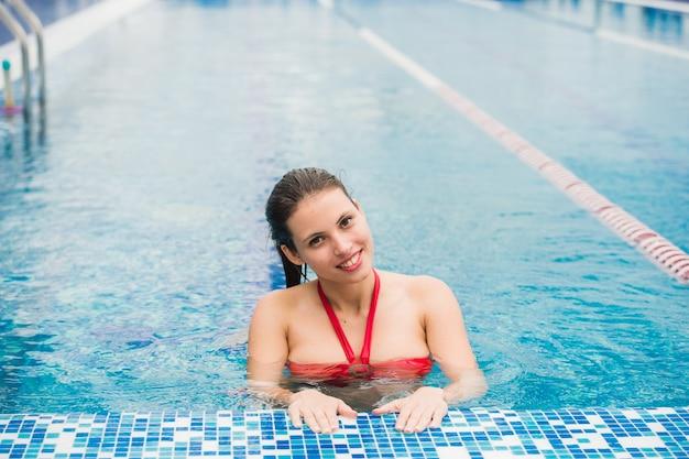 Sexy dame, die rote dessous trägt, die aus dem pool herauskommen