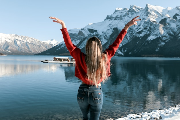 Sexy dame mit schlankem perfektem körper, der am strand nahe dem wintersee steht. weißer schnee liegt auf dem boden und auf den gipfeln der berge. langes blondes haar, das auf der rückseite des roten pullovers liegt.