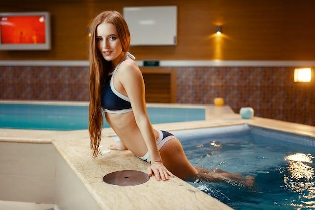 Sexy dame posiert an der seite des pools drinnen