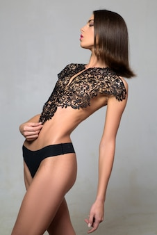 Sexy dessous. attraktive frau. weibliches schlankes modell auf grauem hintergrund. schönes sexy mädchen, das in dessous aufwirft.