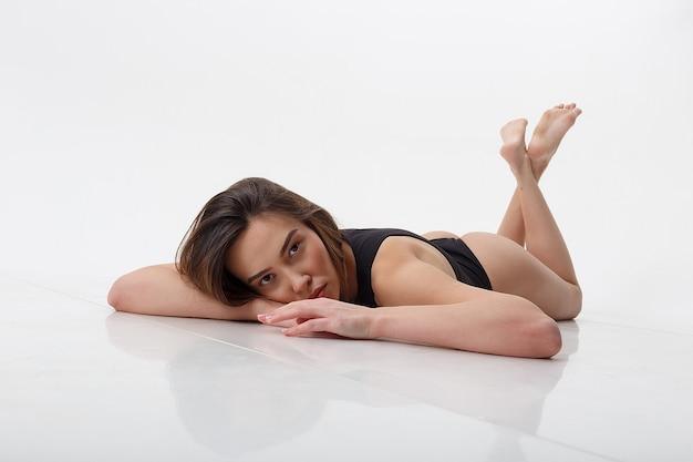 Sexy dünne asiatische hübsche frau liegt auf dem boden auf ihrem bauch in schwarzen dessous