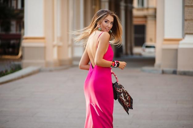 Sexy elegante attraktive frau in rosa sexy sommerkleid langes haar, das in der straße hält handtasche geht