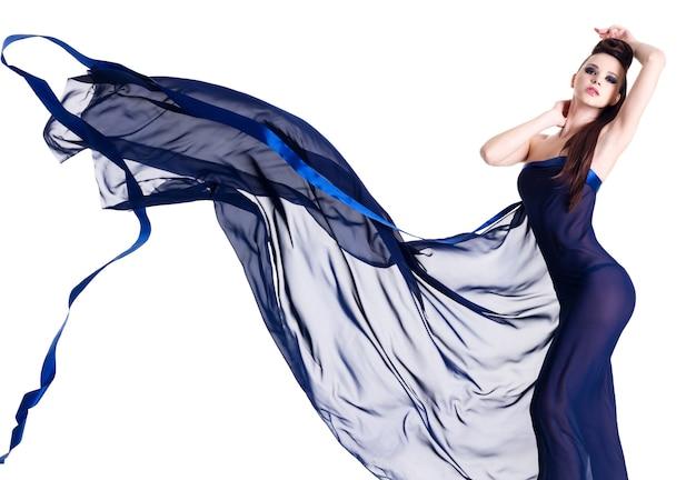 Sexy eleganzmädchen, das im blauen chiffon auf weiß lokalisiert aufwirft