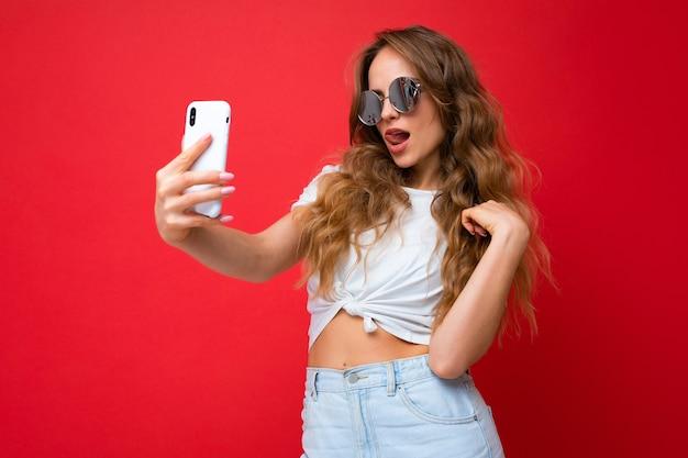 Sexy erstaunliche schöne junge frau, die ein handy hält und ein selfie-foto mit der smartphone-kamera macht