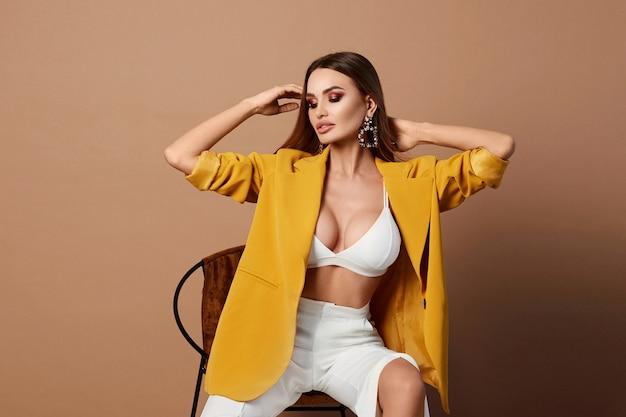Sexy erwachsene frau im stilvollen gelben blazer, der aufwirft