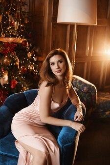 Sexy erwachsene frau in einem abendkleid sitzt in einem sessel nahe dem weihnachtsbaum im luxusinnenraum